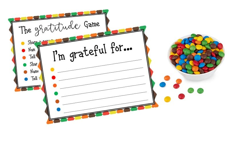 Gratitude Game cards on white background with white bowl of colorful round candies.