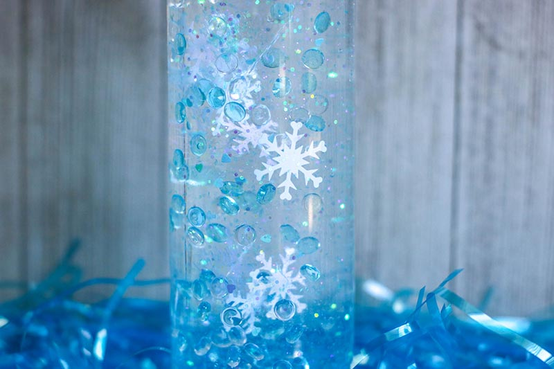 Close up of snowflake confetti, blue fish bowl beads, and glitter slowing descending in plastic bottle.