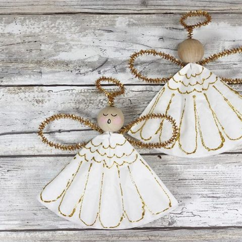 Two finished angel ornaments, one with painted face and one with blank face on white wood background.
