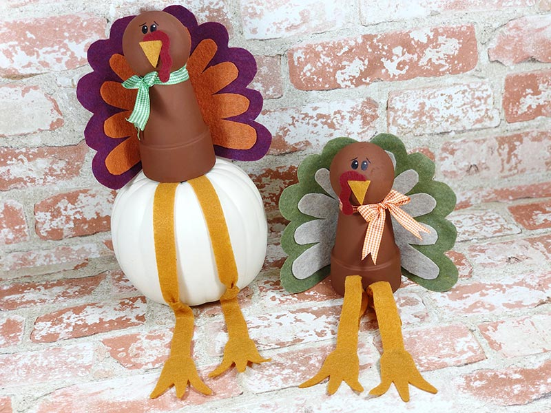 Two completed turkeys made with flower pots and felt feathers on light brick background.
