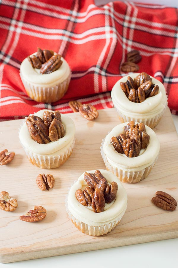 Five cupcakes topped with pecans on a wood cutting board and red flannel cloth.