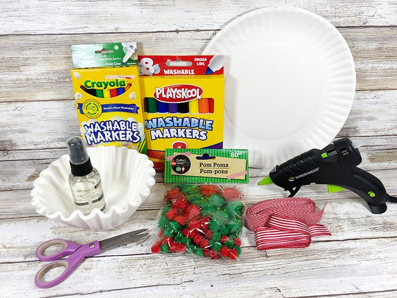 Coffee filters, markers, pom poms, scissors, ribbon, paper plate, and glue gun for craft project.
