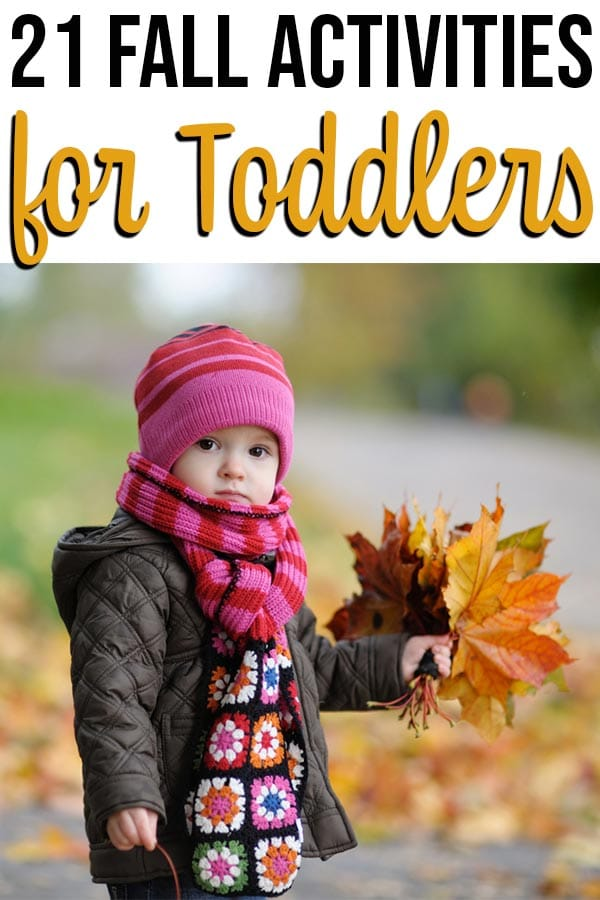 Toddler wearing pink hat, scarf, and coat holding a handful of fall leaves.