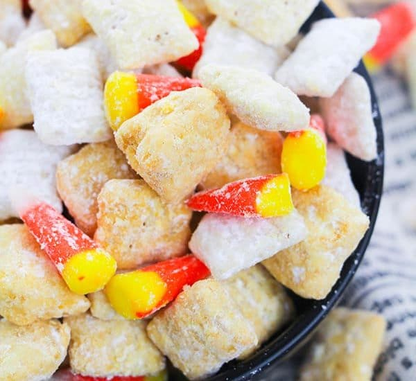 Homemade candy corn puppy chow mix in black bowl on towel that looks like book pages.