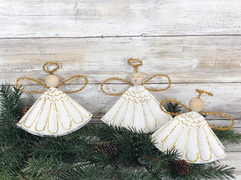 Three completed coffee filter angels sitting on evergreen garland. Middle angel has painted face and the other two have blank faces.