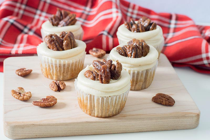 Frosted pecan pie cupcakes on a wood block with pecans scattered around and red plaid flannel cloth.