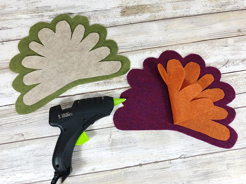Using hot glue gun to glue craft felt together to make turkey feathers. One set is dark green and off white and the other is purple and orange.