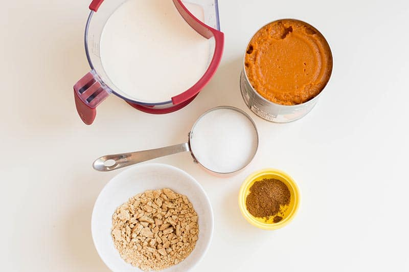 Heavy cream and sugar in measuring cups, open can of pumpkin puree, spices in small yellow bowl, and crushed graham crackers in white bowl.