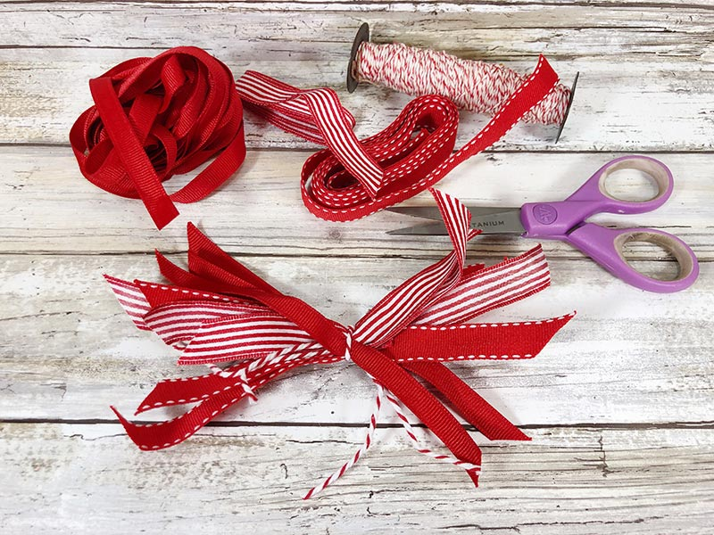 Tying twine around scraps of red and white ribbon pieces to create a bow.