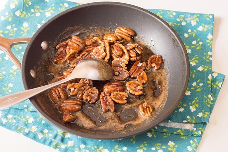 Stirring pecans in brown sugar mixture in a pan.