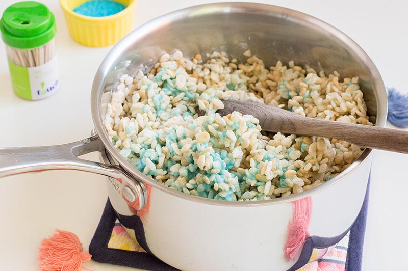 Stirring rice krispies cereal into blue marshmallow mixture in silver saucepan.