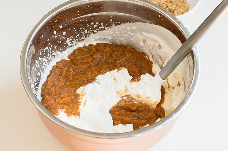Folding whipped heavy cream into pumpkin puree mixture with spatula.
