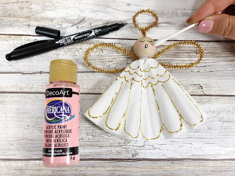 Bottle of pink craft paint and black marker laying next to angel ornament craft. Using cotton swab to apply paint to angel's face.