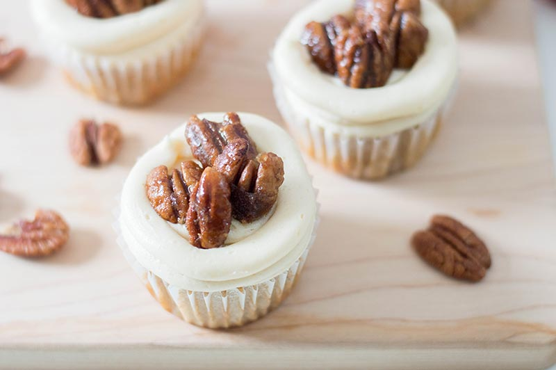 Close up of frosted cupcakes with candied pecans on top.