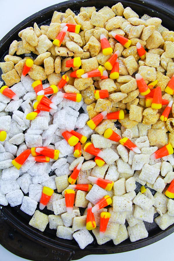 Homemade fall puppy chow recipe with candy corn on a black tray.