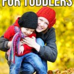 Mom hugging smiling toddler outside while kneeling in pile of leaves. Text overlay at top says 21 fall activities for toddlers.