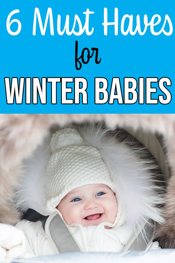 Smiling baby wearing a white winter hat and white coat.