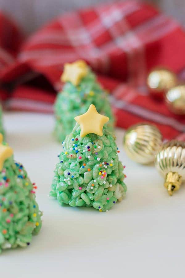 Rice crispy treats that look like Christmas trees standing upright on a white counter surrounded by small gold ornaments and a red plaid cloth.