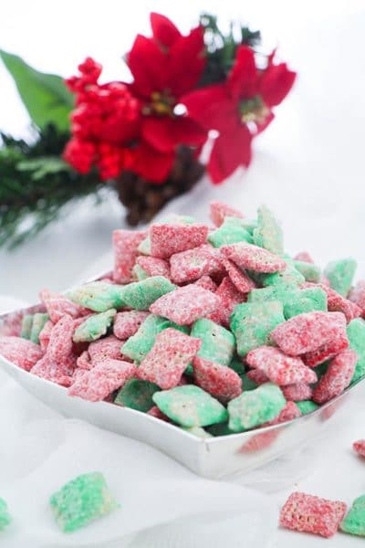 Red and green puppy chow treat made with Chex cereal in silver bowl on white table with red flowers laying behind it.