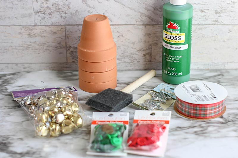 Bag of jingle bells, stack of small clay flower pots, foam paint brush, red and green buttons, green paint, and plaid ribbon for craft project.