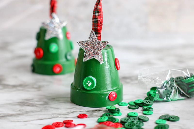 Gluing red and green buttons and glittery silver star to green painted clay pots.