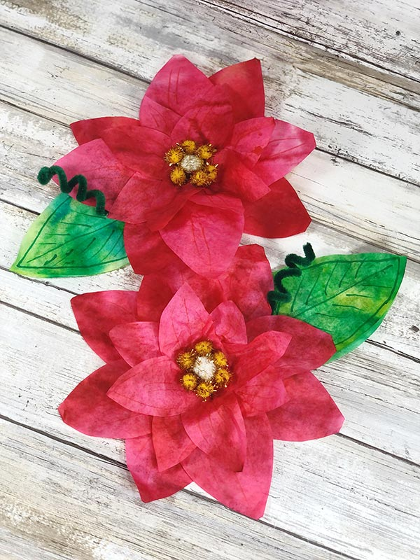 Two completed coffee filter poinsettia flowers laying on a white wood background.