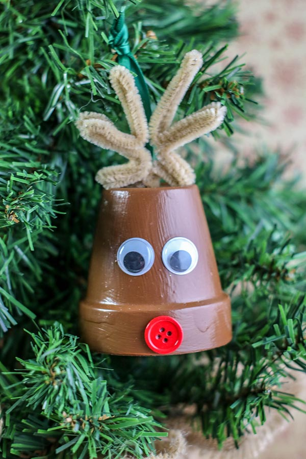 Completed reindeer ornament made with a small clay pot hanging on a small Christmas tree.