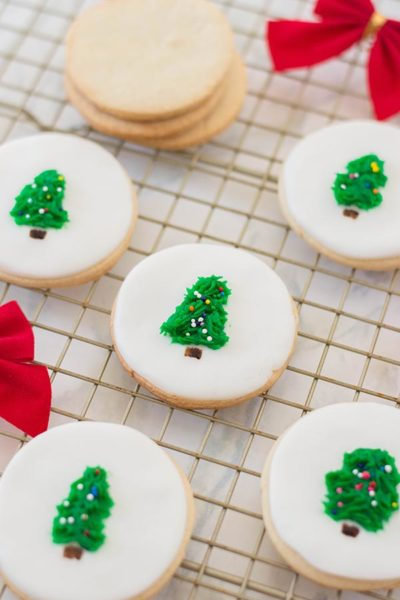 Stack of undecorated round sugar cookies on wire rack next to cookies decorated with white fondant and little Christmas trees in the center.