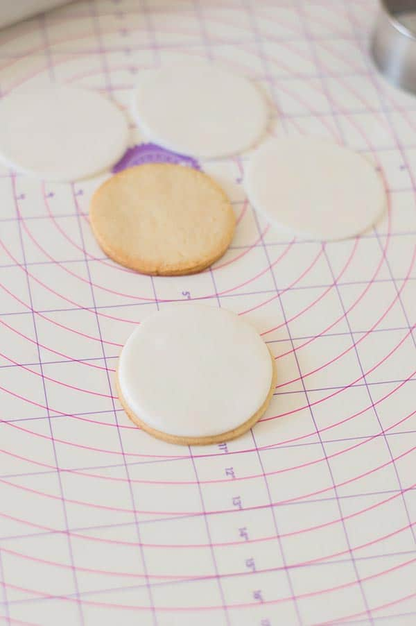 Round sugar cookie and round white fondant cut outs on pastry mat. One fondant circle is on top of a sugar cookie.