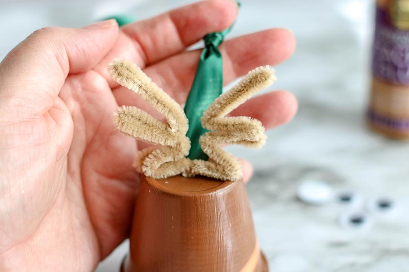 Two tan pipe cleaners shaped like antlers attached to top of clay pot to make reindeer.
