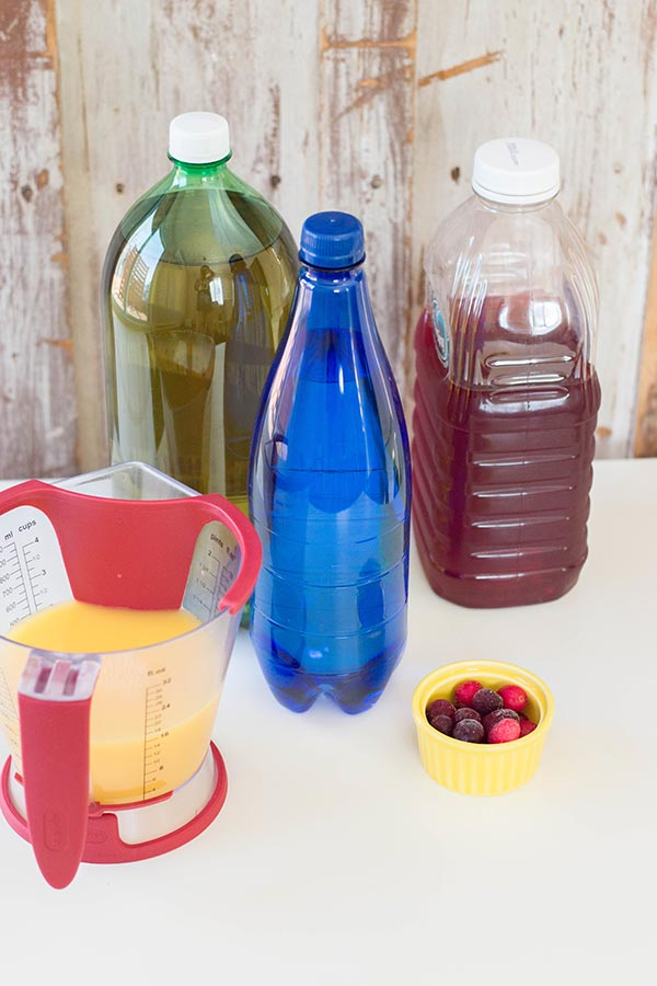 Measuring cup with orange juice, ginger ale bottle, blue bottle of sparkling water, clear plastic bottle of cranberry juice, and small yellow bowl with frozen cranberries on a white counter. Bottles have labels removed.