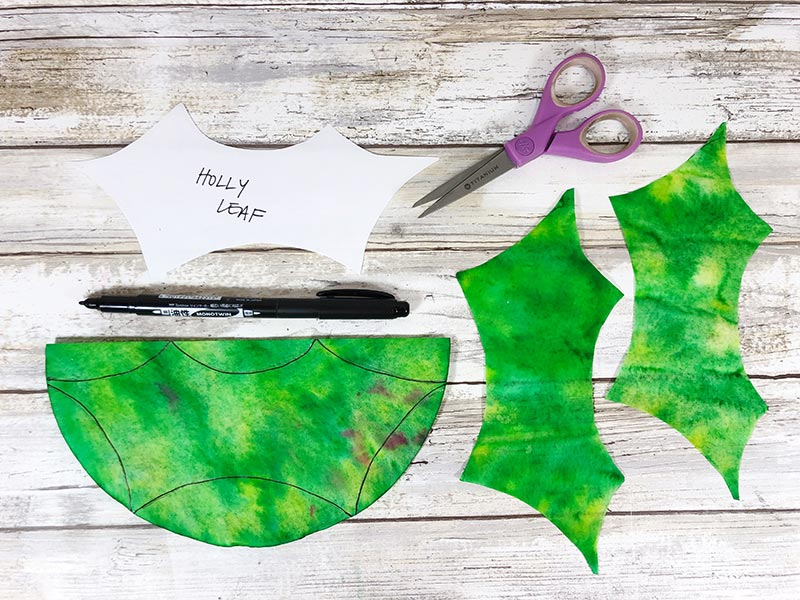 Green coffee filters cut in shape of holly leaves using paper template.