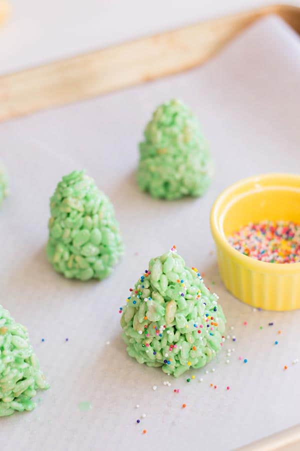 Green rice crispy treats shaped like trees standing on wax paper. Small yellow ramekin with rainbow nonpareils sprinkles in it and some sprinkled over the treats.