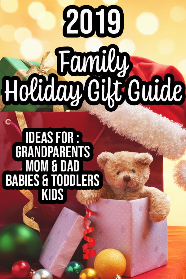Pile of presents, teddy bear popping out of one gift, and a Santa hat on a table. Yellow bokah background and text overlay describing gift guide.