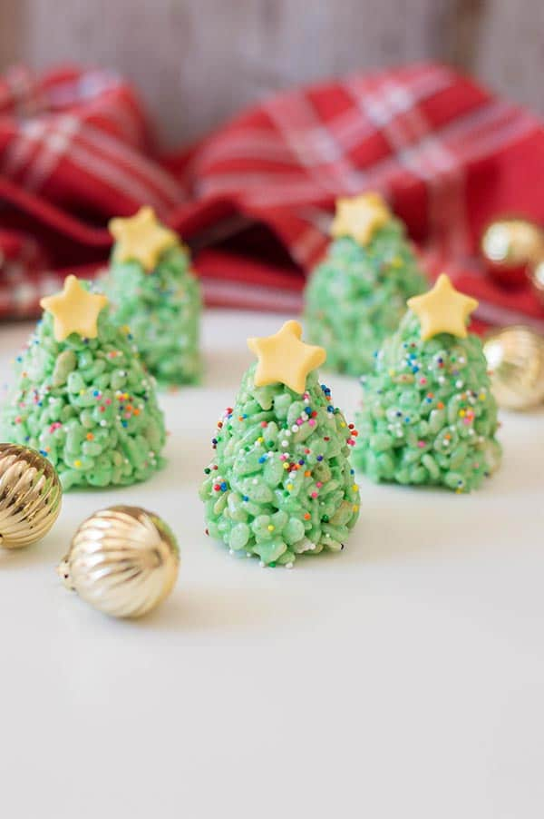 Green rice crispy treats shaped and decorated like Christmas trees with rainbow sprinkles and yellow fondant star on top. Treats are standing on a white countertop with small round gold ornaments and red plaid cloth around them.