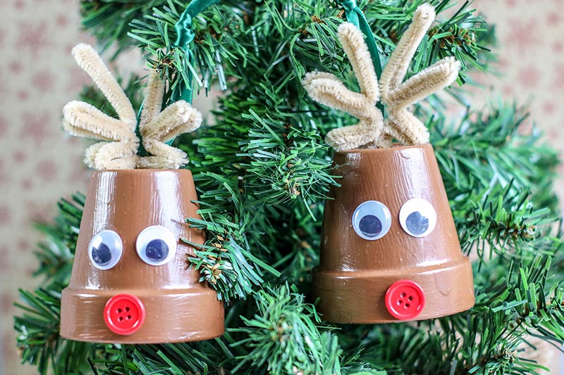 Two completed reindeer clay pot crafts hanging from small tabletop Christmas tree.