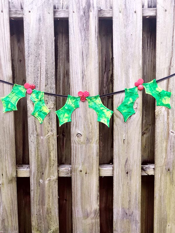 Ribbon banner with three coffee filter holly leaves and berries hanging along a wooden fence.