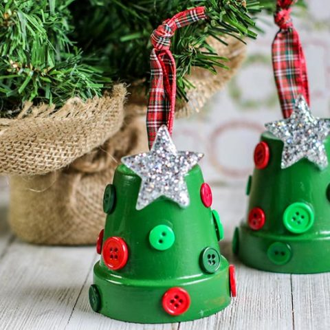 Completed clay pot Christmas Tree ornaments sitting side by side on table next to mini evergreen tree.
