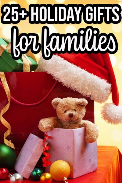 Pile of presents, teddy bear popping out of one gift, and a Santa hat on a table. Yellow bokah background and text overlay that says 25+ Holiday Gifts for families.