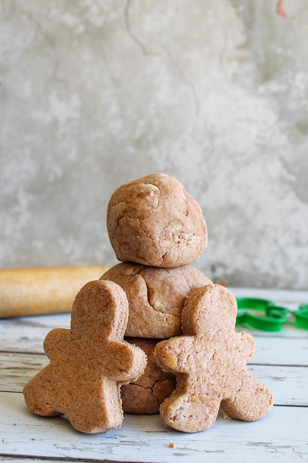 Brown playdough balls stacked up with gingerbread men cut out of playdough leaning against them.