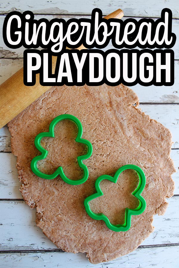 Light brown gingerbread playdough rolled out flat. Rolling pin laying across top of playdough with gingerbread boy and girl cookie cutters on top of dough.