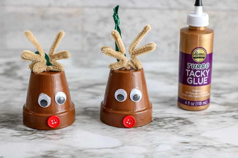 Adding googly eyes and red button noses to flower pot using craft glue.