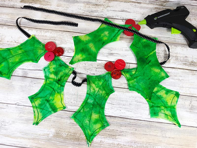 Gluing coffee filter holly to black ribbon with glue gun.