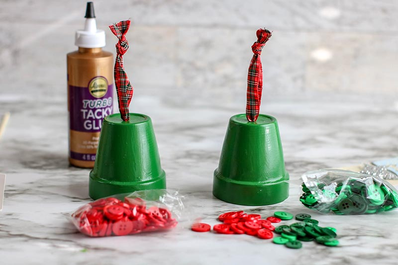 Two green painted clay pots set upside down with plaid ribbon coming out of hole. Red and green buttons and craft glue next to them on the table.