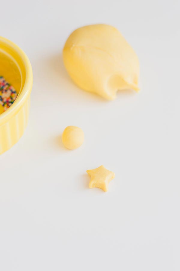 Ball of yellow fondant and another piece of fondant shaped into a star.