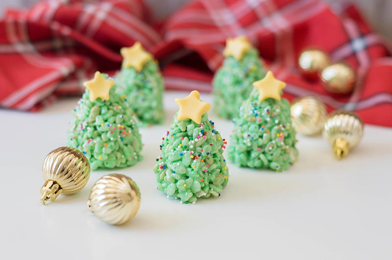 Five completed Christmas tree rice crispy treats with yellow fondant stars on top. Trees are standing up on a white counter with a plaid cloth in back and small golden ornaments scattered around.