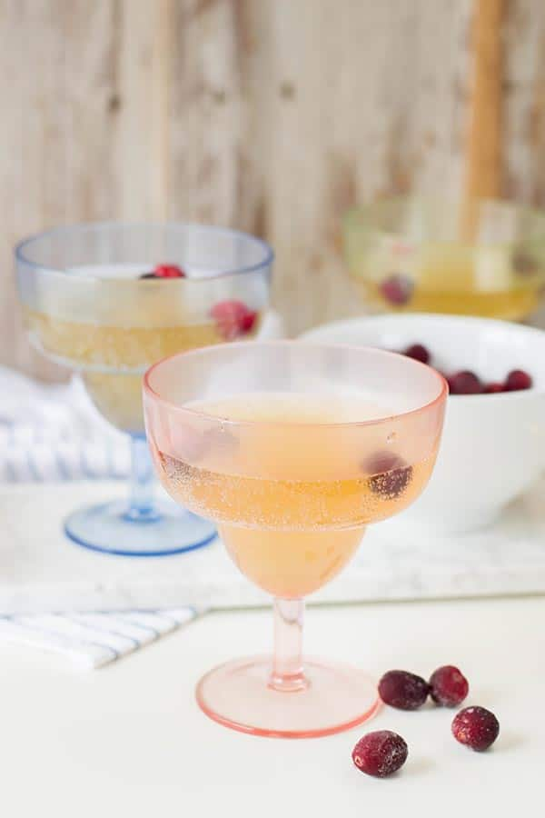 Two cocktail glasses with sparkling pineapple drink and frozen fruit on a white counter.