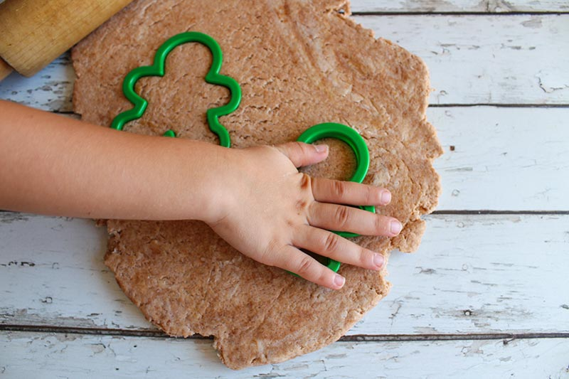 Light brown playdough rolled out with rolling pin and kid hand pressing green plastic gingerbread men shaped cookie cutters into it.