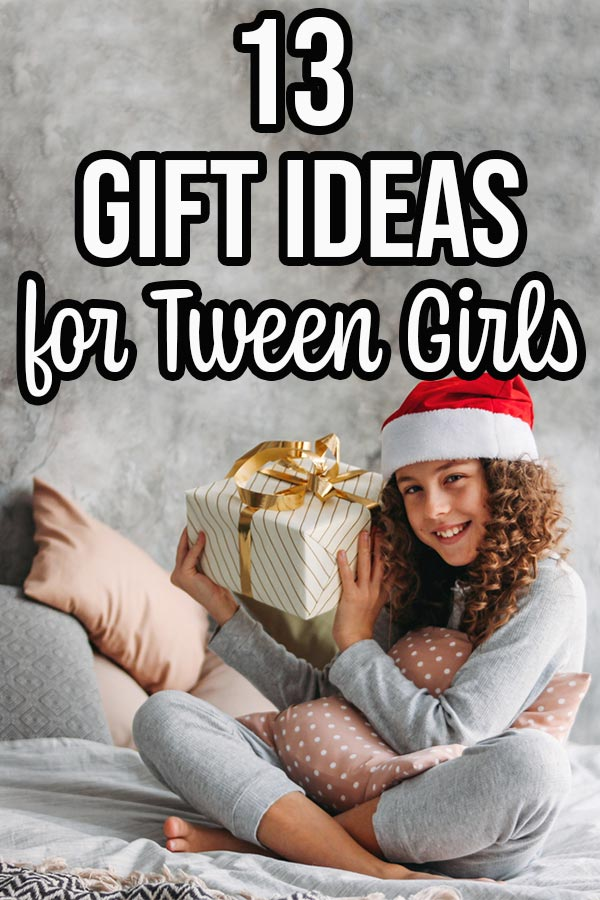 Tween girl sitting on bed holding wrapped present and wearing a Santa hat.
