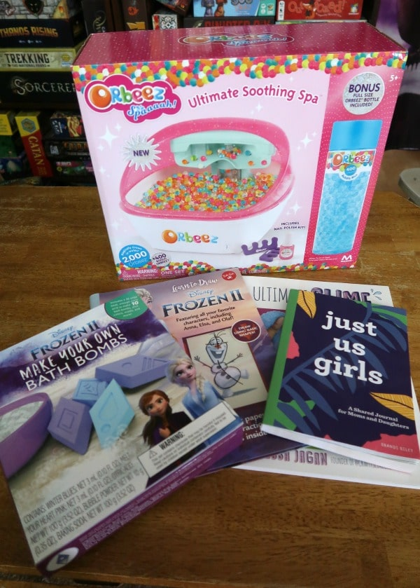 Orbeez foot spa, bath bomb kit, slime book, and mother daughter journal laid out on wooden table.